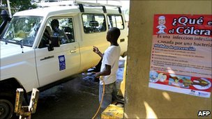 Dominican health worker disinfecting a UN vehicle as it crosses the border from Haiti, 27 October 2010