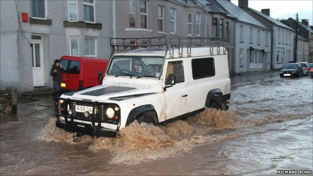 car drives along flooded road in St Blazey, Cornwall