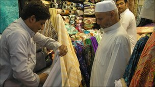 A man shows fabric to another man in a market in Mecca