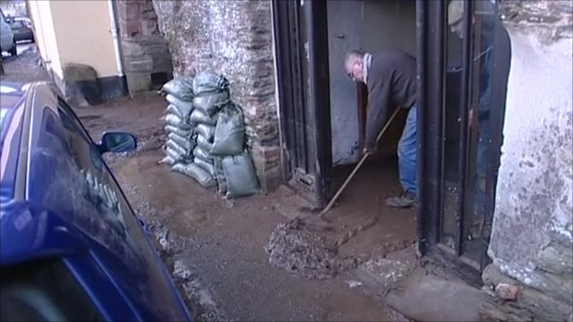 Resident clearing up the mud in Lostwithiel