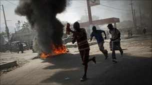 Demonstrators run past burning tyres in Port-au-Prince, Haiti, Thursday, 18 November.
