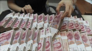 Chinese bank teller handling piles of yuan notes