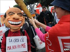 "Protester dressed as Berlusconi wearing sign saying ""There is a crisis but not for me"""