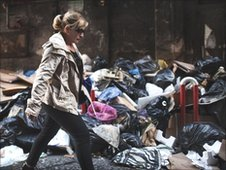 Woman walks past rubbish in Naples