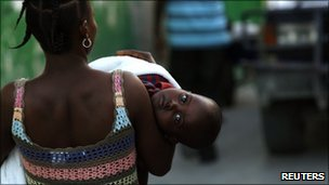 A woman carries her child suffering from suspected cholera in Port-au-Prince, Haiti (19 Nov 2010)