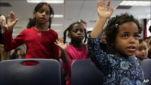 Yasmin Long, 8, left, from St. Lucia, Jessika Lionel, 6, from Haiti, and Mirette Franklin, 4, from Ethiopia, all adopted children, repeat the pledge of allegiance, 18 November 2010, in New York