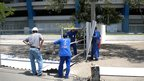Workman start on a section of fencing around the stadium