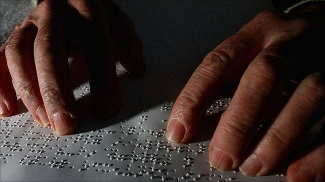 A man reading braille