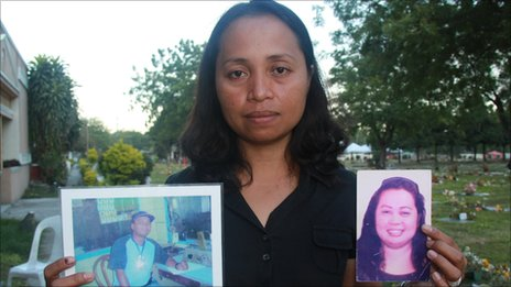 Grace Morales holding pictures of her husband and sister who were killed in the Maguindanao massacre, picture taken November 2010