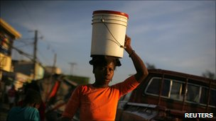 A girl carries a bucket of water in Port-au-Prince on 21 November