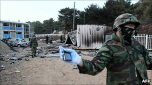 A South Korean soldier prevents photographers from approaching the ruins of a bombed-out military residence area on Yeonpyeong island