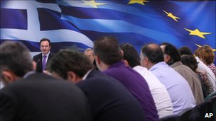 Greek Finance Minister George Papaconstantinou, seen behind journalists, speaks during a news conference in Athens on 23 November 2010