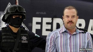 Drugs suspect Carlos Montemayor in chains, guarded by a masked police officer
