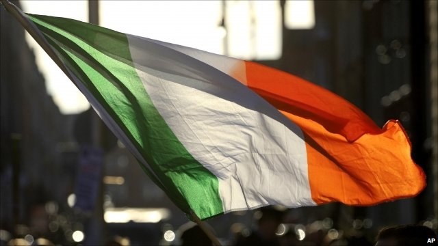 Irish flag being waved outside government buildings in Dublin