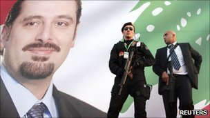 Turkish and Lebanese security men stand in front of a poster of Lebanon's Prime Minister Saad Hariri