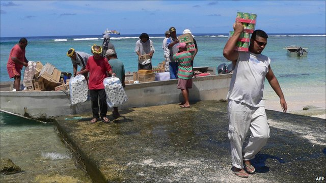 People unloading goods from a boat on Nukunonu atoll, one of the islands in Tokelau in the Pacific