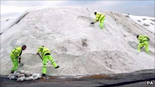 Contractors work on a 27,000-tonne mound of marine salt in Dagenham