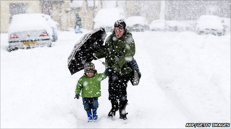 Woman and child walking through snow