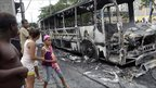 Residents watch a bus burned by alleged drug traffickers at the Santa Cruz slum in Rio de Janeiro.