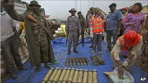 Nigerian soldiers and officials showing some of the arms seized at Apapa seaport in Lagos, 27 October 2010