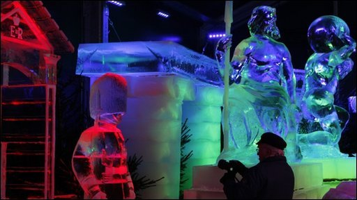 "A man taking a picture of a sculpture made out of a large block of ice at the Snow and Ice Sculpture Festival under the theme ""Around the World"" in Bruges"