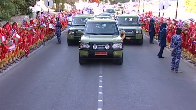 People line the street as the Queen is transported by car