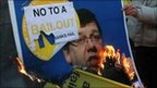 Protesters burn a placard with a picture of Irish Prime Minister Brian Cowen