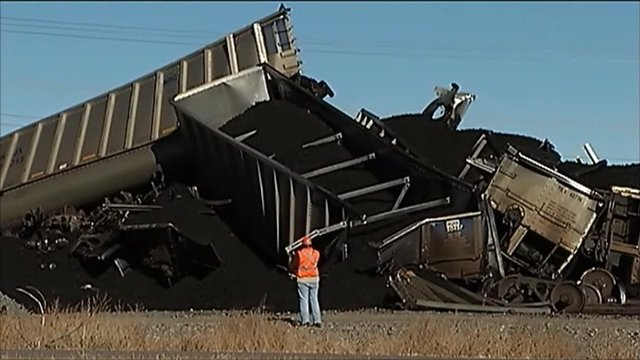 Worker looking at freight train wreckage