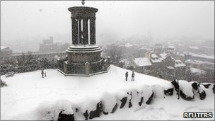 People stand in the snow on Calton Hill in Edinburgh