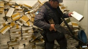 A policeman holds one of hundreds of marijuana packs found inside a house in the Alemao complex