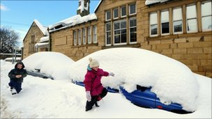 Children play next to a row of cars covered in snow in Alnwick, Northumberland, as heavy snowfall continues across the North East