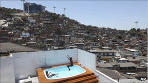 Local children play in a swimming pool after police finish their search of a house of an alleged drug dealer in Complexo do Alemao