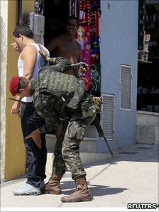 Soldier frisks a man in Complexo do Alemao on 29 November
