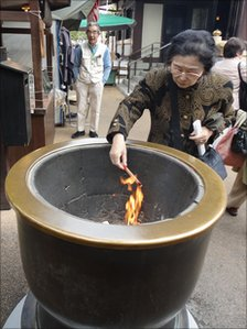 Woman outside temple in Sugamo, praying for long life and good health