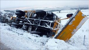 A snow plough delivering grit in the Scottish Highlands slips and overturns