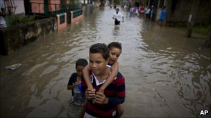 A boy carries a girl on his back through the flooded streets of Higuerote, Venezuela