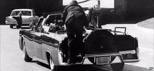 Clint Hill jumps on JFK's car as it speeds away moments after the assassination