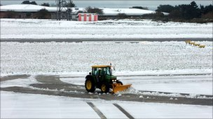 Tractor works on clearing snow from Guernsey Airport runway