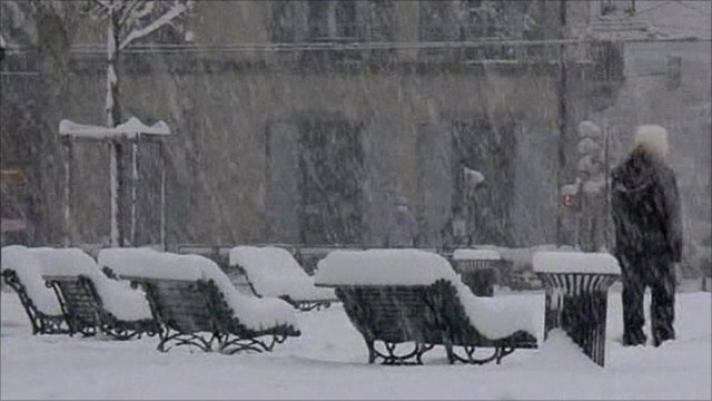 Benches in city square covered in thick snow