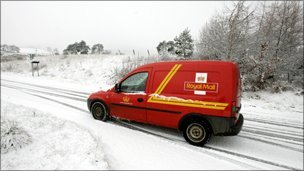 A Royal Mail post van struggles through the snow