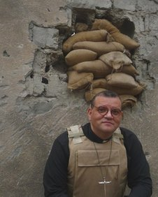 Canon Andrew White by a blasted wall in Iraq