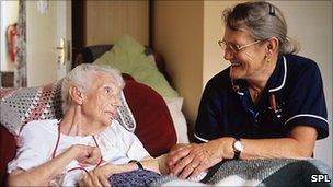 Smiling nurse talking to elderly patient