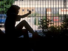 A young girl in silhouette next to some railings