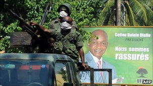 Presidential guard soldiers pass in front of a poster featuring Guinean presidential candidate Cellou Dalein Diallo on 2 December 2010 in Conakry