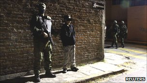 A soldier escorts the suspect in Cuernavaca December 3, 2010.