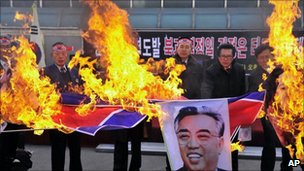 South Korean military veterans burn a North Korean flag and portrait of Kim Il Sung, the late founder of North Korea, at a rally in Jecheon, South Korea, 3 December 2010