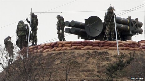 "South Korean marines stand beside the self-propelled surface to air missile system ""Cheonma"" on Baengnyeong island near the western maritime border between the two Koreas, 3 December 2010"