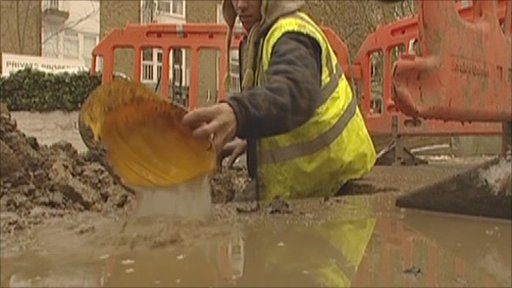 Man dealing with burst pipe in south west London