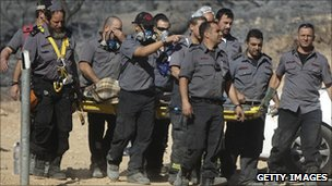 Israeli firefighters carry the body of a dead colleague, 3 December 2010