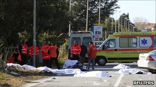 Medics inspect the bodies of eight cyclists killed in a collision with a car near Lamezia Terme in Italy (5 December 2010)